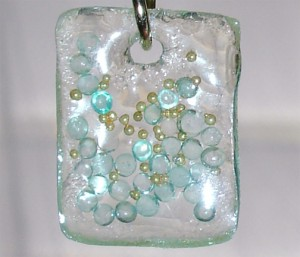 closeup of resin square with blue glass beads and gold beads